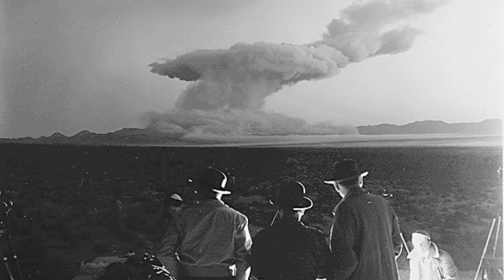 An archive black and white photograph of an above-ground nuclear test in the US desert, with three men looking on.